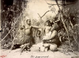 Staged portrait of an Aboriginal Australian family dressed in tradtional attire. The man is pointing in accusation at the woman, who cradles a baby with noticeably pale skin. These staged photographs say more about the photographer and European conceptions of Indigenous people than about the traditional practices of Indigenous people themselves. The people in this image are members of Tommy McRae's community.